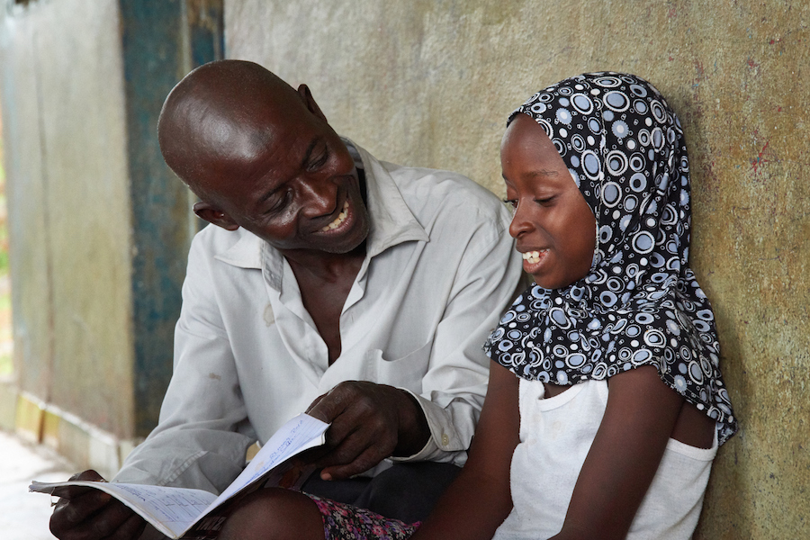 Sulaiman Samura checks the homework of his daughter Fatmata, 10 years old in the the suburb of Hilltop, Freetown, Sierra Leone on May 30, 2017.