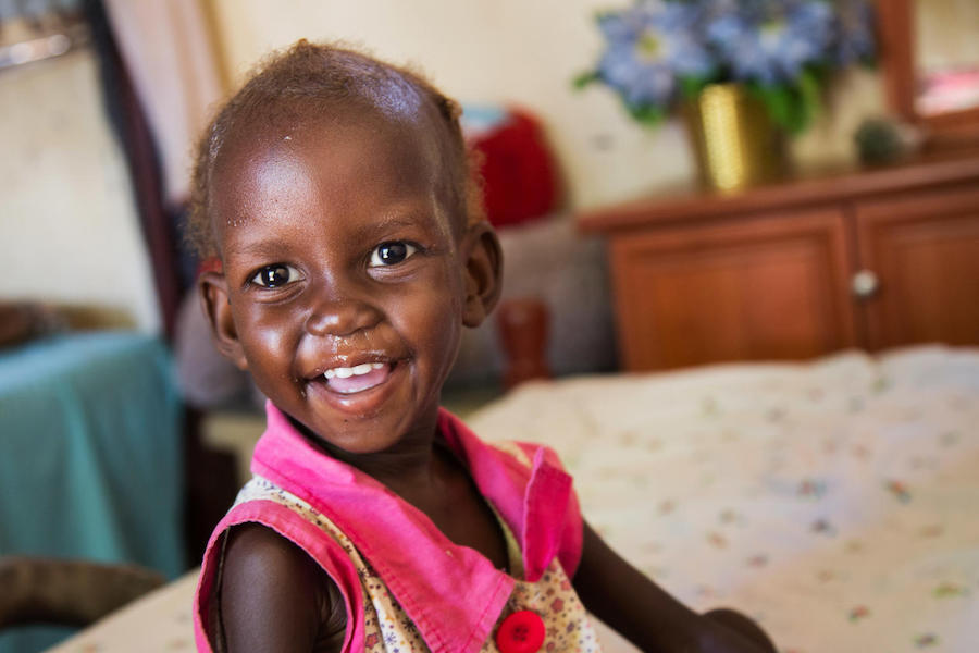 Maria, 2, who was diagnosed with severe acute malnutrition, smiles after her ration of Ready-to-Use Therapeutic Food at her family's home in Juba, South Sudan in November 2017.