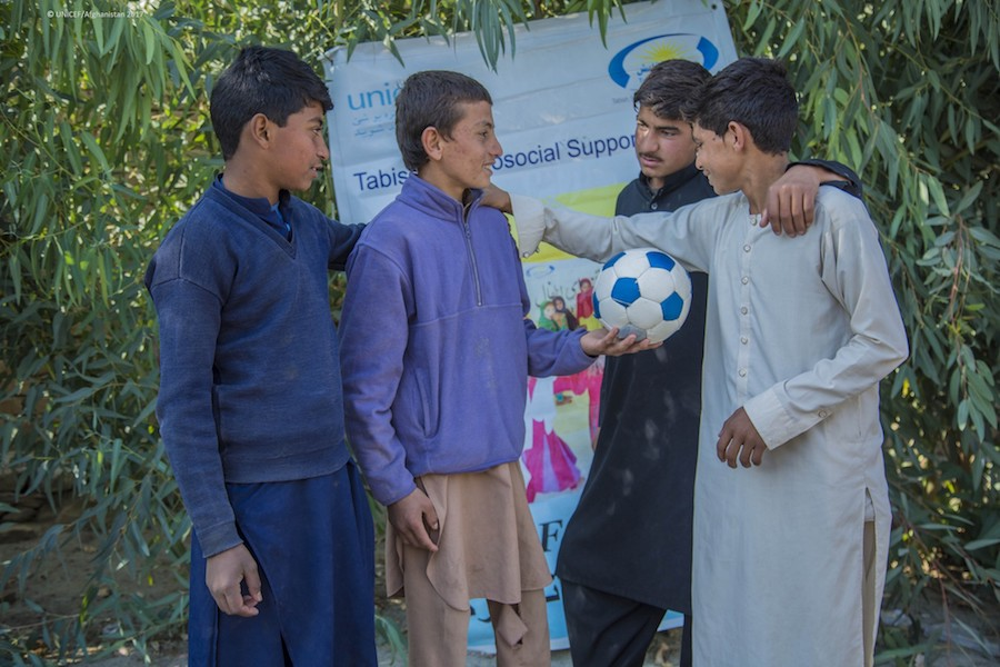 Meeraj, 13, holds a soccer ball and talks with friends at the UNICEF-supported Child-Friendly Space in Ettifaq village, Nangarhar province, Afghanistan in 2017.