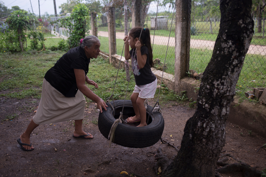 Conzuelo pushes her great-granddaughter Allizon, 4, on a home-made swing in Cayo District, Belize, August 2016. Because Allizon's mother works full time, Conzuelo is Allizon's primary caregiver and spends many hours interacting with her every day.