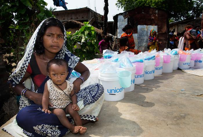 A woman and her child wait to receive relief items distributed by UNICEF, including a treated mosquito net and blankets, in Dhangar Tole ward no. 12, Gaur Municipality, Rautahat District, Nepal, Tuesday 22 August 2017.