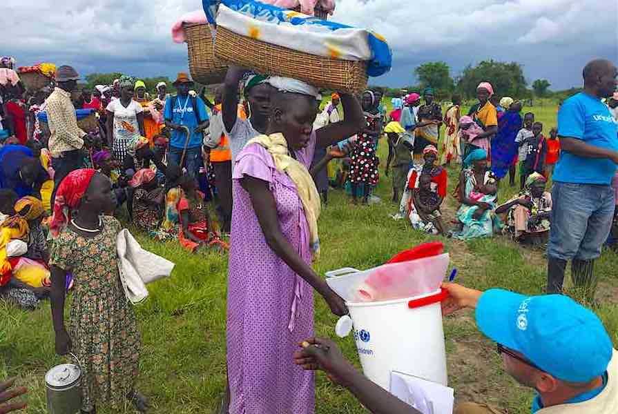UNICEF staff distribute WASH supplies, including buckets, soap and water purifiers, to pregnant women and lactating mothers, during a Rapid Response Mechanism (RRM) mission in Kaikuiny village, Jonglei State, South Sudan, Friday 25 August 2017. UNICEF and