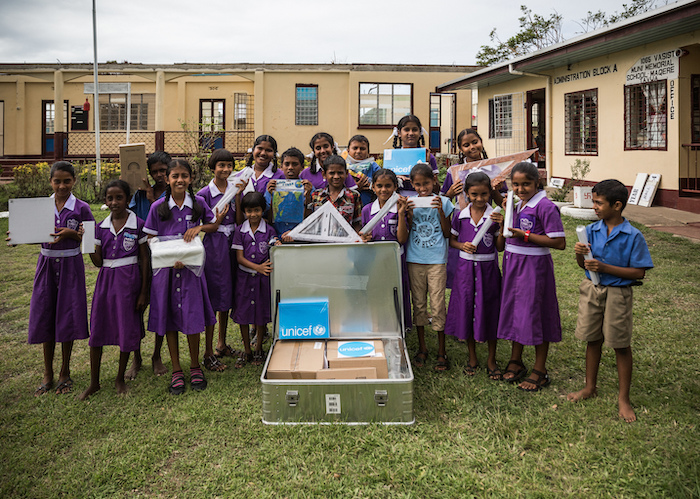 Students of Vasist Muni Municipal School in Fiji display the contents of a School-in-a-Box kit provided by UNICEF in March, 2016.
