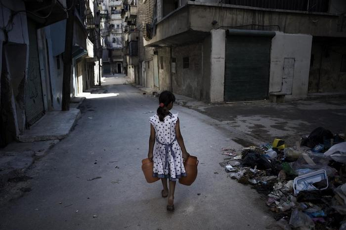 A girl carries water through the streets of Aleppo, Syria, where attacks on water and sanitation services have been a signature of the country's armed conflict.