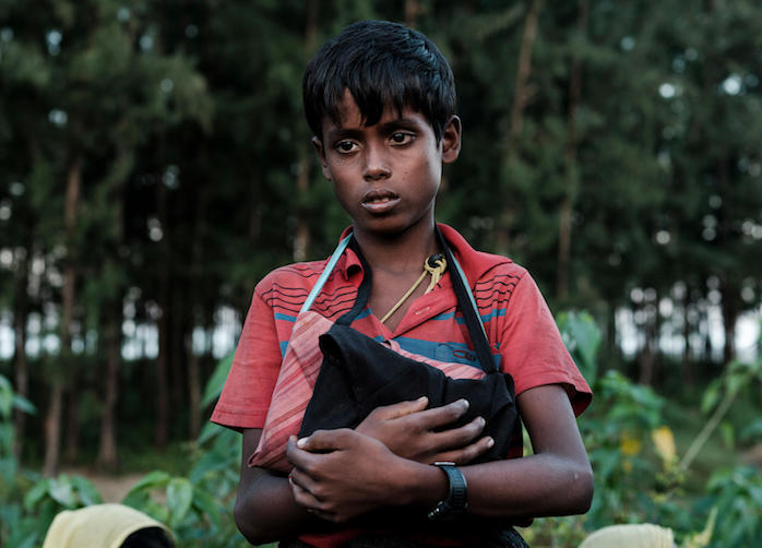 In Cox's Bazar, Bangladesh, 10-year-old Rohingya refugee Mohammed clutches two copies of the Holy Quran, the only belongings he has left after he fled ethnic violence in Myanmar in 2017.