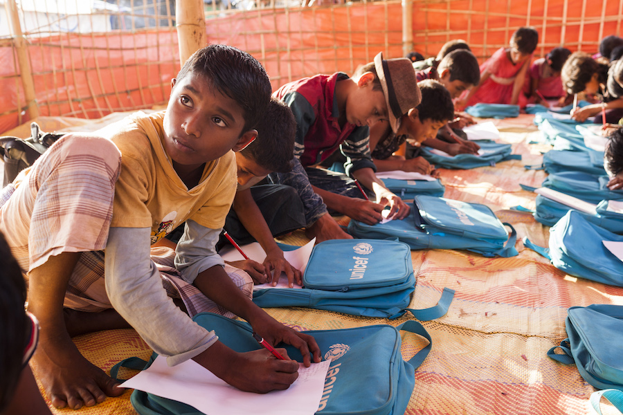 Rohingya refugee Rahmat Ullah, 12, who fled Myanmar by walking nonstop for two days and two nights with his family to the Myanmar-Bangladesh, attends a class at the Thainkhali makeshift settlement in Cox's Bazar, Bangladesh