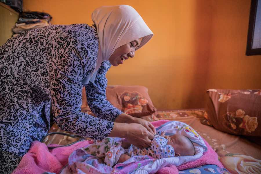 Laticia, 20 days old, is checked by midwife Widyani during a home care visit in Batu, Indonesia. Widyani also delivered the child.