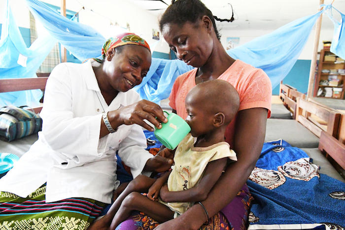 At a UNICEF-supported health center in the village of Zouan Hounien in northwestern Côte d'Ivoire, nurse Blandine Tonga helps a 32-year-old grandmother feed therapeutic milk formula to 3-year-old Doris, who is dehydrated and severely malnourished.