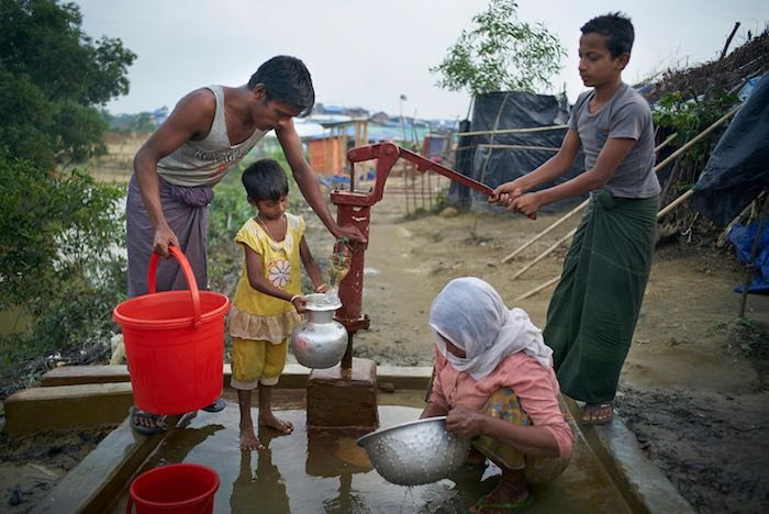 (Left) Fariduallah, 25, collects water from a community hand pump in the Madhu Chara area of Kutupalong makeshift settlement in Ukhiya Upazila, Cox's Bazar District, Bangladesh,