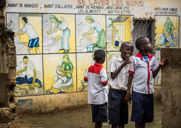 Students stand beside a mural illustrating the importance of handwashing in Kinshasa, Democratic Republic of the Congo.