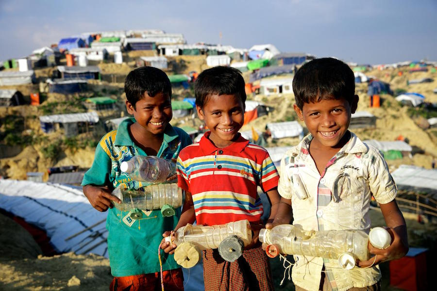 In December 2017 in Bangladesh, three smiling boys hold toy cars they made from discarded objects in a makeshift Rohingya refugee settlement in Ukhia sub-district, in Cox's Bazar district.