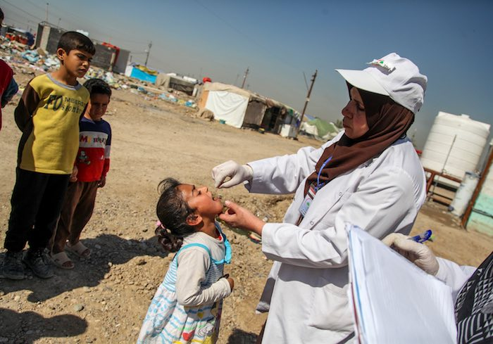 A health worker administers a dose of oral polio vaccine to a child in Baghdad's Al-Takya Al-Kasnazaniya Camp.