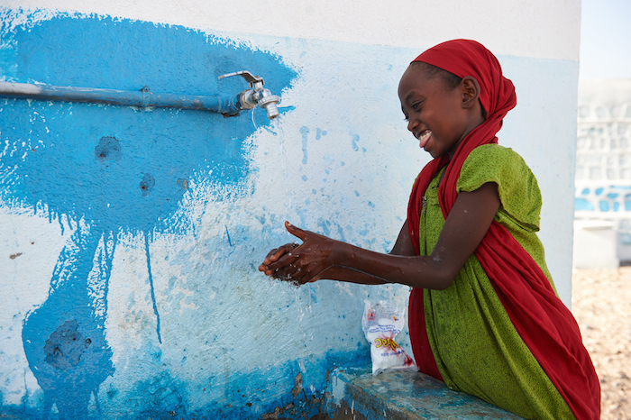 A girl wash her hands with soap and tap water outside a UNICEF-supported school in the village of Dafo, outside Tadjourah, southern Djibouti.