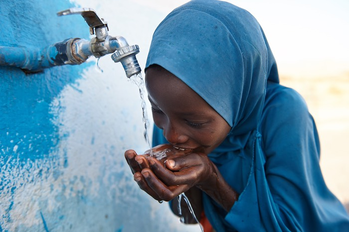 Since 2014, UNICEF has improved 51,000 schools' water, sanitation and hygiene facilities and services for students like this girl who drinks safe water from a tap outside a UNICEF-supported school in Djibouti. © UNICEF/UN0199510/Noorani