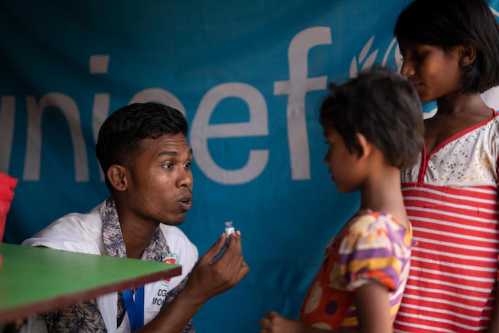 Vaccinator Chutan Das holds an empty vaccine vial as he explains what a cholera vaccine is to two girls at a vaccination site run by the Bangladesh Ministry of Health in Balukhali camp, Cox's Bazar, Bangladesh in May 2018.
