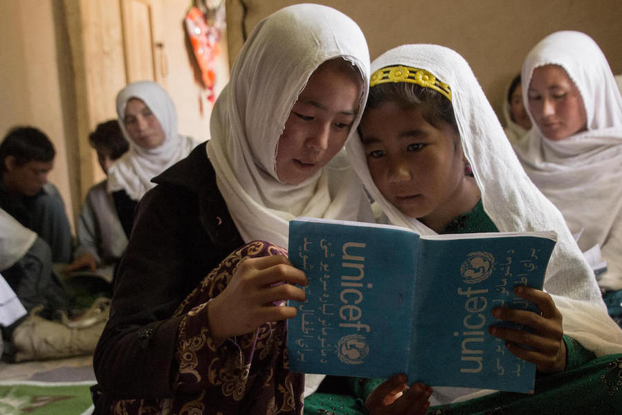 Two girls read from a shared notebook at the UNICEF-supported Accelerated Learning Center in Sharak e Muhajireen village in Nili district, Darikundi province, Afghanistan.