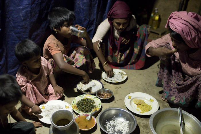 A family breaks sunset fast during Ramadan in Modurchara Camp 5, part of the sprawling Rohingya refugee settlement in Cox's Bazar, Bangladesh on June 4, 2018.