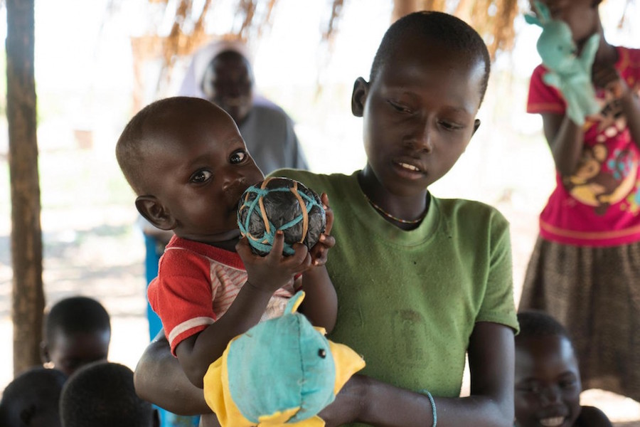 Carried by her older sister, a baby plays with a homemade ball in Bidi Bidi, a refugee camp in northern Uganda's West Nile region in May 2018.