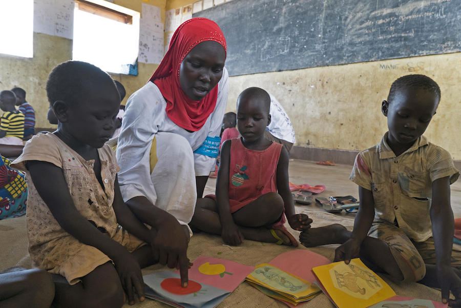 Ugandan caregiver Dalla Alli, 28, shows locally made cardboard books to South Sudanese refugee children in Bidi Bidi refugee settlement.