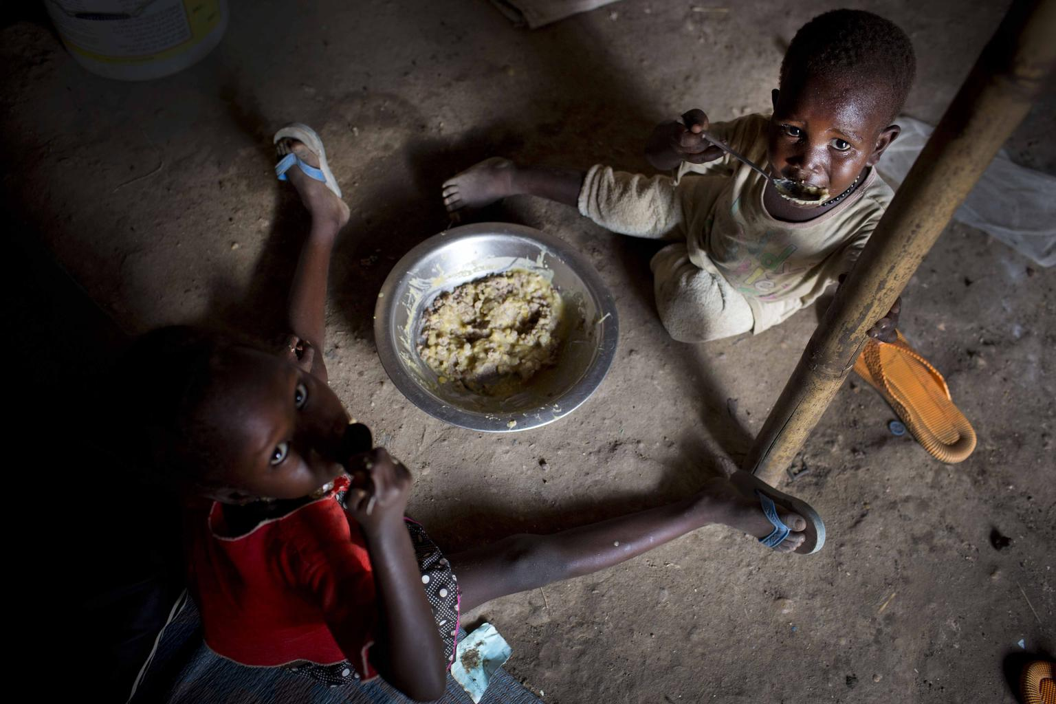 Children displaced by recent fighting eat their daily meal at a displacement site in Juba. © UNICEF/NYHQ2014-0344/Kate Holt