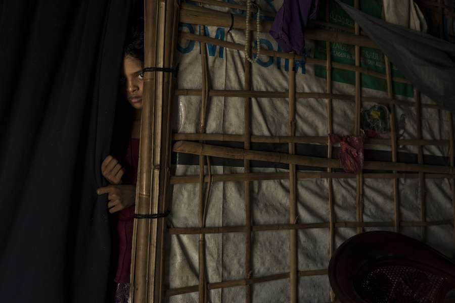 A young Rohingya Muslim girl, peers from behind a curtain in her family shelter in the Bulankuli refugee camp, Cox's Bazar, Bangladesh on 22 July, 2018.