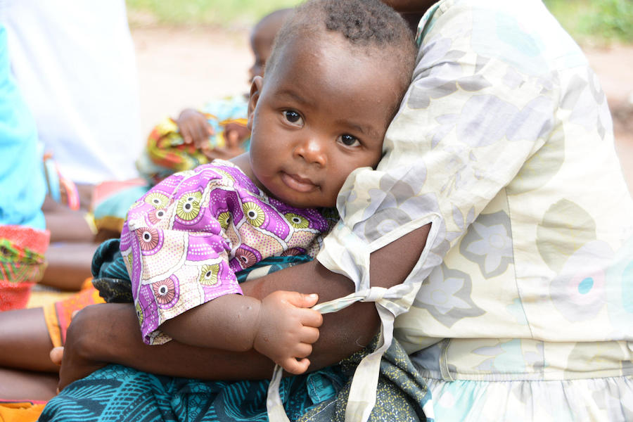 A baby snuggles in her mother's arms outside the UNICEF-supported Mkoko Village Clinic in Phalombe, Malawi in 2018.