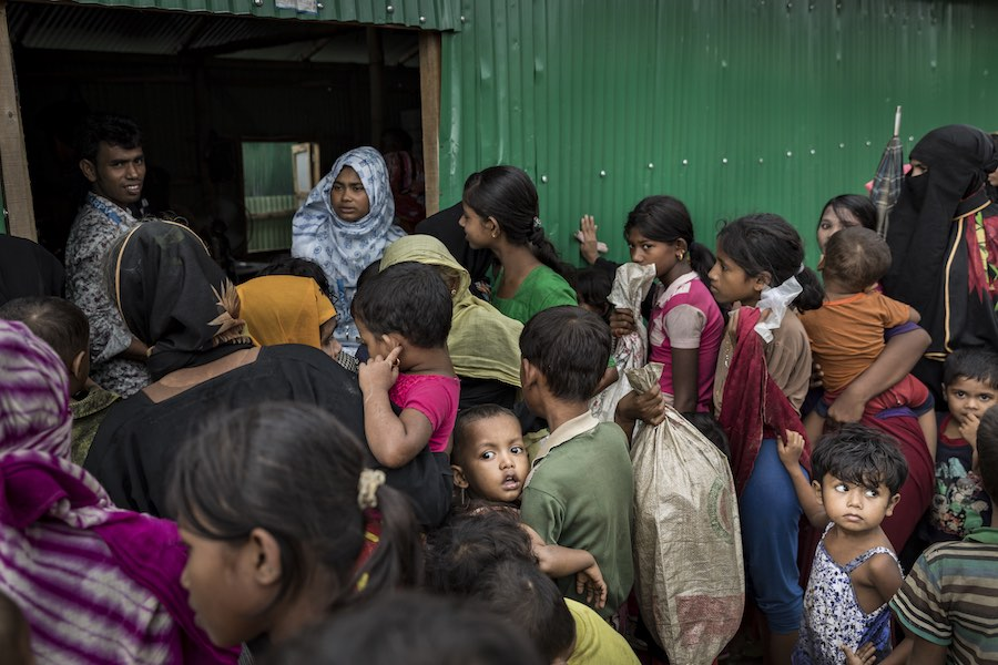 On 1 August 2018 in Cox's Bazar in Bangladesh, Rohingya women and children wait to receive aid from the one of the many aid distribution aid stations in the Unchiprang refugee camp.