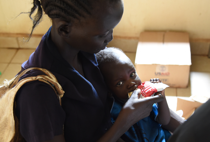 At Rumbek Hospital. Ayen Kuac is helping her daughter Yar Makoi with the appetite test. The test helps the health workers determine how severe the malnutrition is. Yar Makoi is seventh months old and Ayen's number six. Ayen explains how she has breastfed