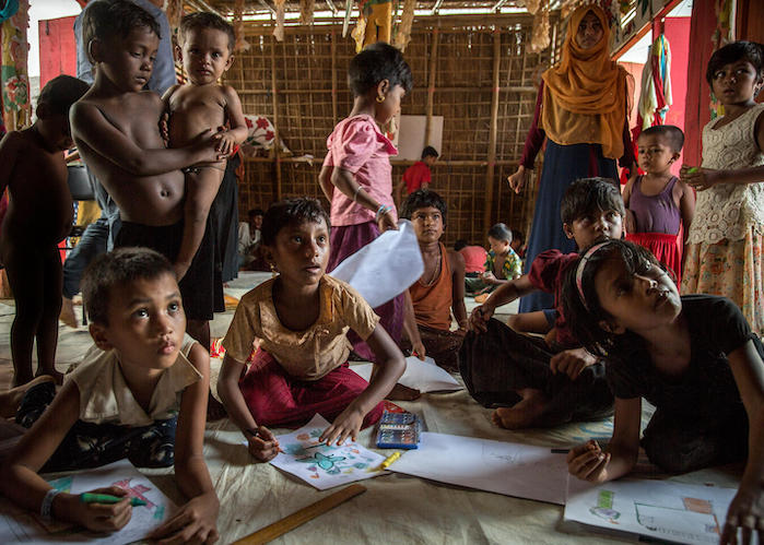 Rohingya refugee children draw pictures in a UNICEF Child-Friendly Space in BaluKali Camp 1, Bangladesh in September 2018.