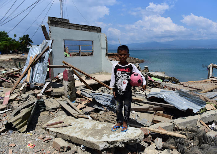 In Donggala, Central Sulawesi, Indonesia, 10-year-old Rido stands in front of his home, ruined by a tsunami in September 2018.