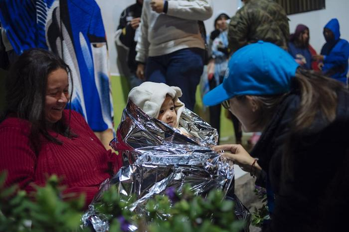 A UNICEF worker wraps a baby from Venezuela in a thermal blanket in Rumichaca, on the Ecuador/Colombia border.