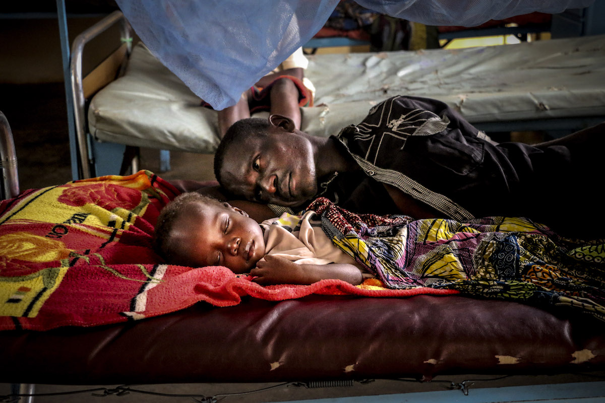 On 19 July 2018 in the Central African Republic, Pierre Mbassissi and his father in bed at the malnutrition stabilisation centre at the Bangui Paediatric hospital.