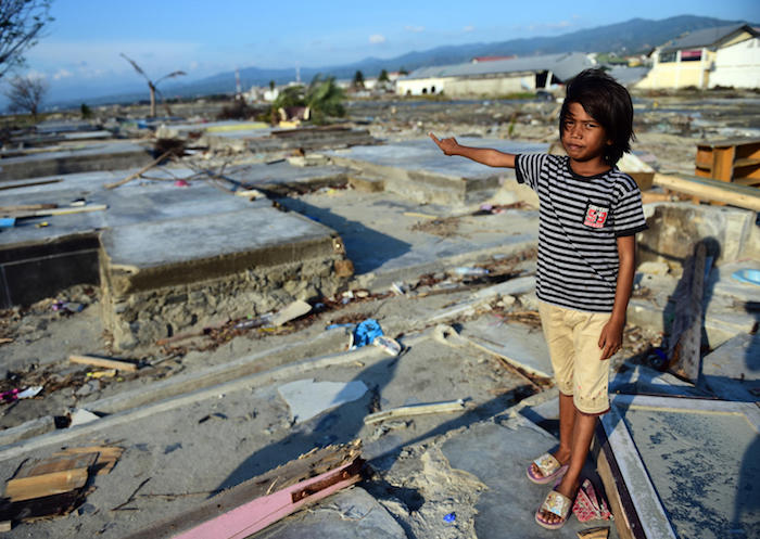 In Talise village, Palu, Indonesia, 9-year-old Tasya points to the ruins of her home, destroyed by the 2018 earthquake and tsunami.