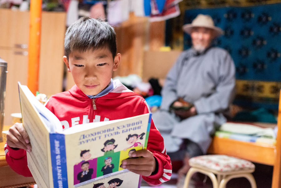A special needs student reads a book at his house in Altai, Gobi-Altai province, Mongolia in September 2018. UNICEF has developed a sign language book for deaf children.