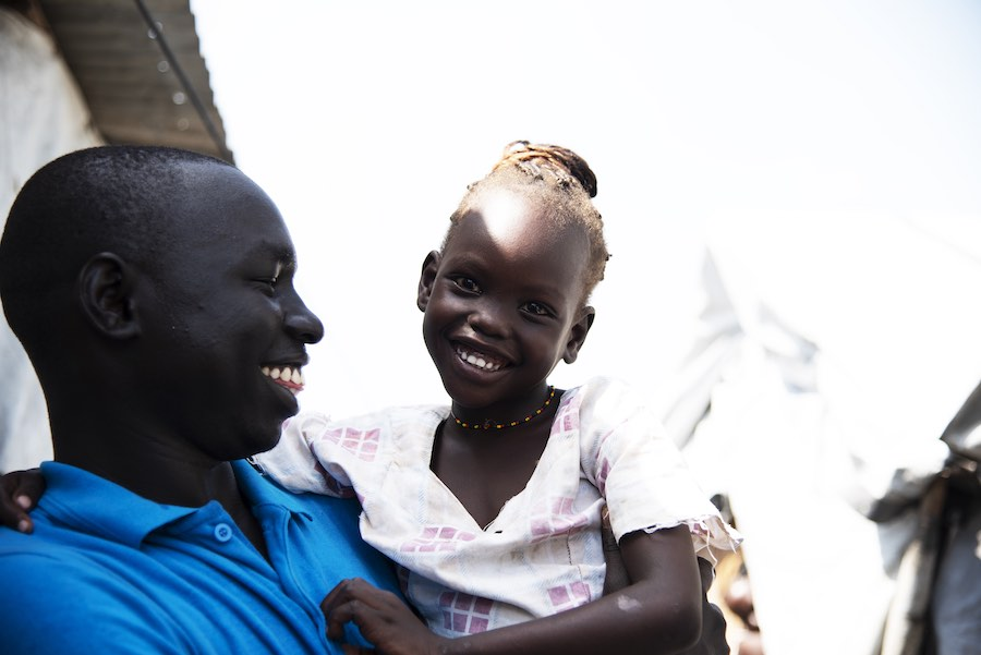 "Simon Char with five-year-old Nyajiper Iwany in his arms. She has been separated from her parents for more than four years. Recently her father was found in Bor and Nyajiper will be reunited with him in just a few weeks. ""I've told her that she will soon"
