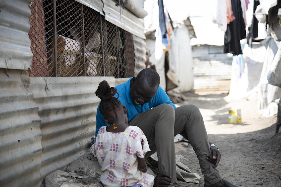 Simon Char, a UNICEF caseworker, plays with 5-year-old Nyajiper. UNICEF recently found Nyajiper's father, and the two will be reunited soon.