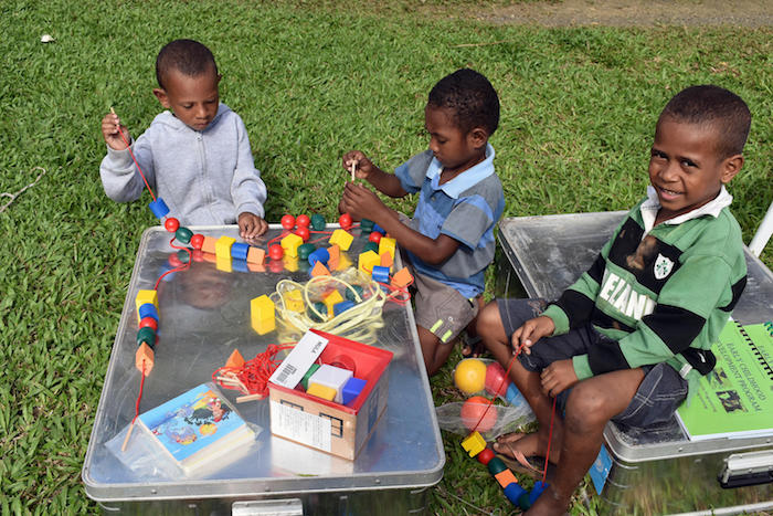 Children in Alotau, Papua New Guinea explore the contents of a UNICEF School-in-a-Box kit in July, 2018.
