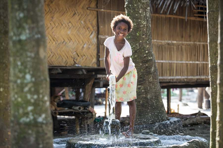 A young girl pumps water from an underground water source at Dugumor Village, Bogia District, Madang Province, Papua New Guinea.