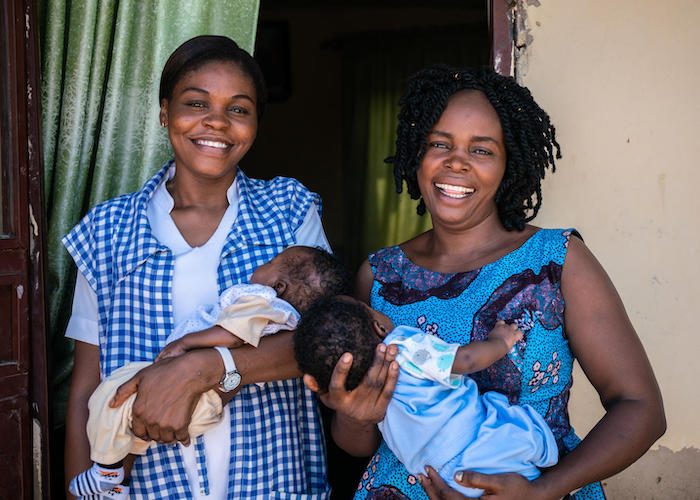 UNICEF-supported health worker Amilia Mathew (left) and her sister hold twins delivered at their local clinic  in Yola, Nigeria in October 2018.