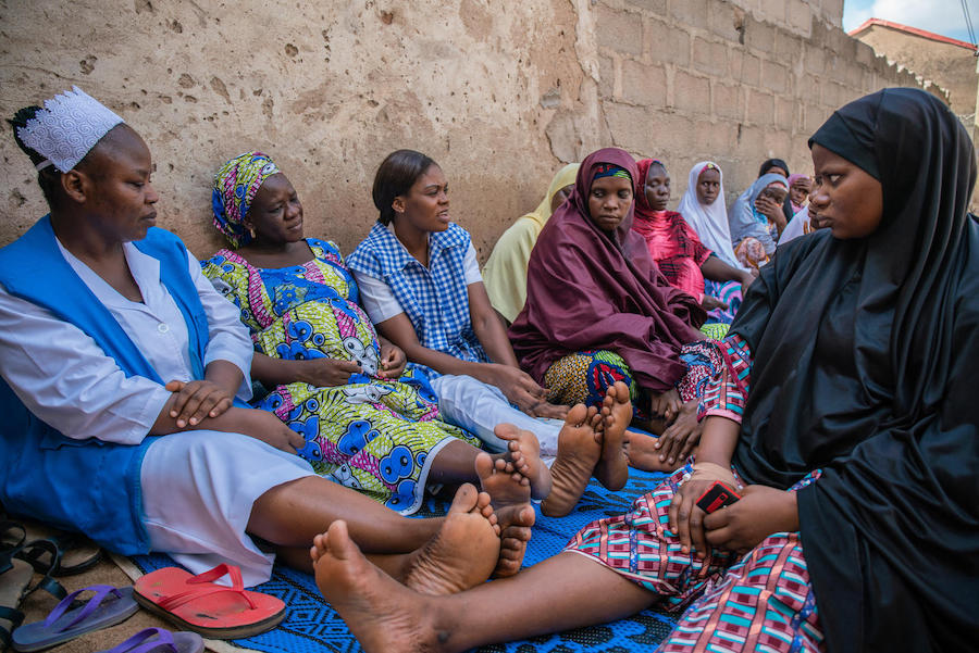 Amilia Mathew (center, in her checked uniform) advises pregnant women and mothers on health issues during a community outreach activity in Yola, Nigeria in November 2018.
