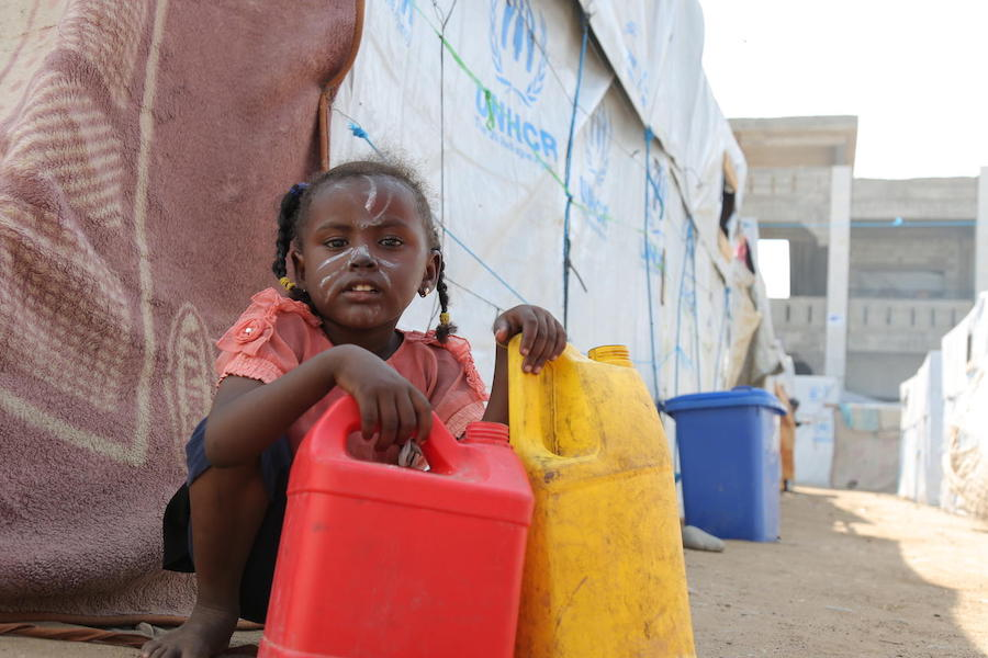 A girl holds containers used for carrying water at a camp for internally displaced persons in Aden, Yemen on December 4, 2018.