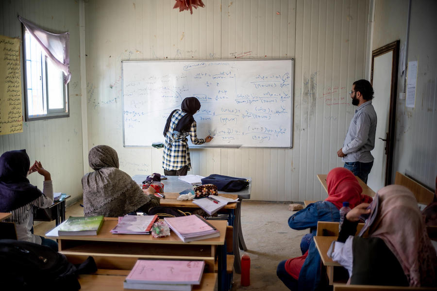 Syrian refugee Bodoor, 17, writes an equation on the white board in class at a UNICEF-supported remedial education center in Azraq refugee camp, Jordan, in 2018.