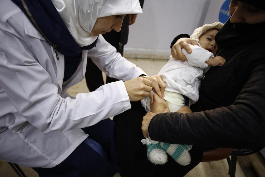 In December 2018, an infant is vaccinated at the Eastern Douma Primary Health Center operated by the local department of health and supported by UNICEF in East Ghouta, Syria.