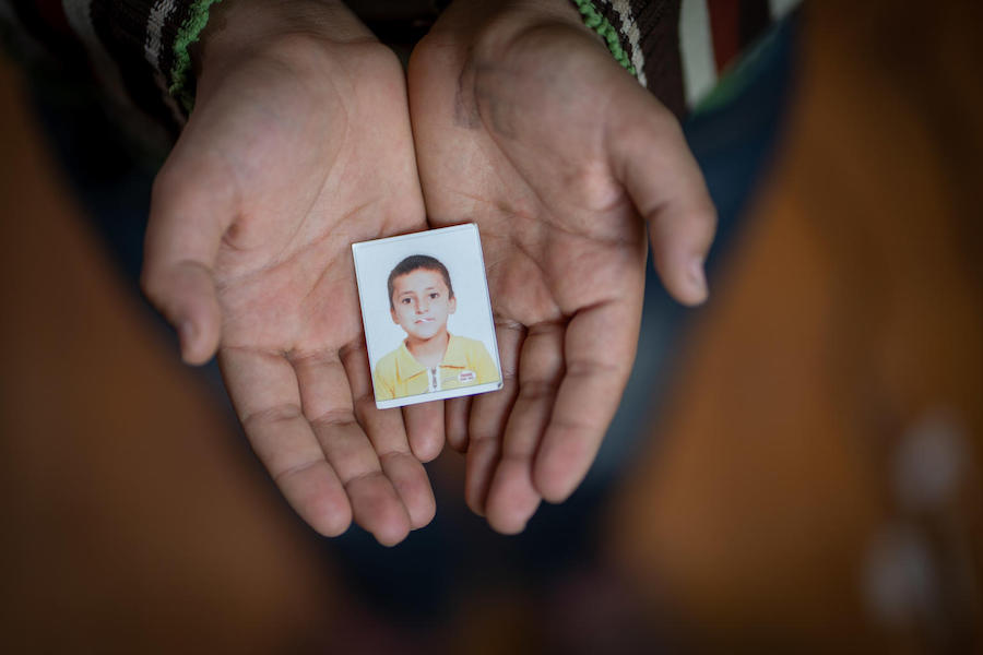 Yahya, 13, holds an old passport photo of himself in Za'atari refugee camp.