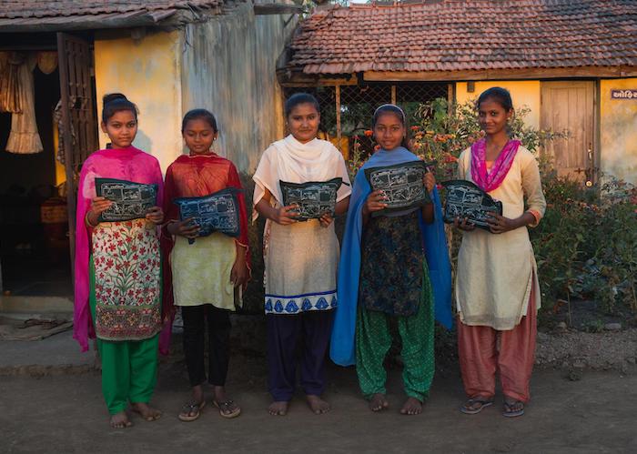 .Adolescent girls at a residential ashram school in Khamar Village in Gujarat, India hold menstrual hygiene kits they received from UNICEF partner organization Seva Rural.