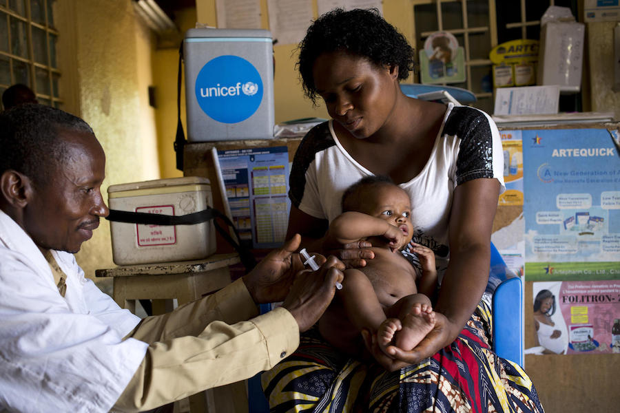 UNICEF-supported health worker Nsiri Lowoso vaccinates Zoe, 3 months, with the MMR (measles, mumps and rubella) vaccine as his mom, Arellete Ytshika, holds him in Lubumbashi, Democratic Republic of Congo on November 10, 2018.