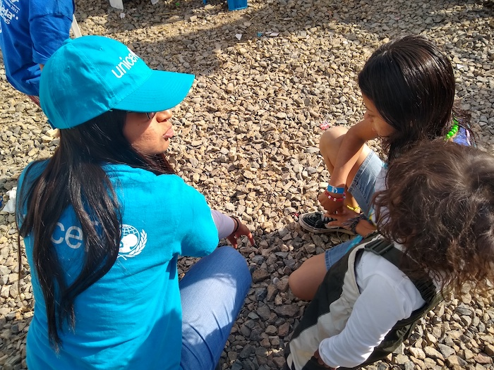 A UNICEF volunteer engages with migrant children from Central America staying at the 'El Barretal' shelter, Tijuana, Baja California state, Mexico.