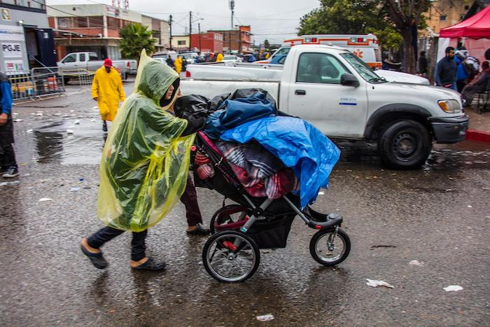 A family migrating from Central America to the U.S. leaves a makeshift shelter during a rain storm in Tijuana, Mexico.