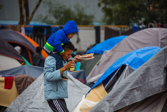 A father and his child walk through a tent city serving as a temporary shelter for migrants in Tijuana, Mexico.