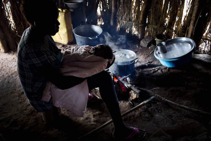Esther, 18, holds her baby as she prepares food inside her home in Yambio, South Sudan.